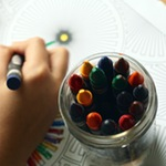 Jar of crayons and child colouring