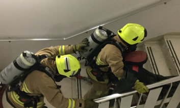 Two firemen carry dummy downstairs