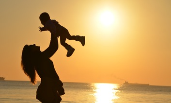 Mother holds up child on sunset beach