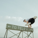 male jumping over sign reads to telelscope