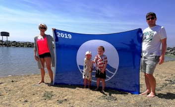 Carlie Crease and partner Tom Cook, hold blue flag up behind their children on Three Shells beach.