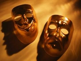 Two golden masks, the one of the left is smiling and the one on the right is frowning