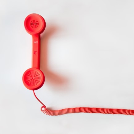 Red Handset receiver of landline telephone.