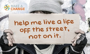 Sign held up with text: help me live a life off the street, not on it.