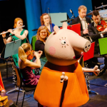 Peppa Puppet in front of orchestra.