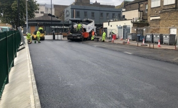 Resurfaced area to become Pitmans Car park with machinery working in the distance.