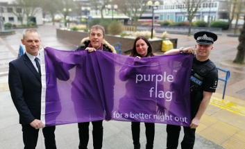 Carl Robinson, Southend-on-Sea Borough Council, Cllr Mark Flewitt, Alison Dewey, BID and Insp Ian Hughes holding purple flag outside Civic Centre.