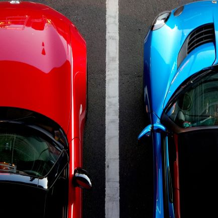 Top down view of red and blue cars parked side by side