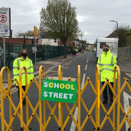 Two people standing in front of School Street barrier in High Vis jackets at Westleigh Leigh School