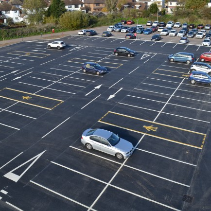 Overhead view of newly complete carpark with several cars parked in spaces