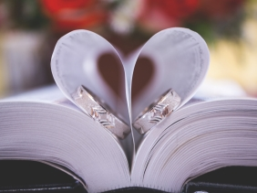 Two rings on book with pages folded over in heart shape.