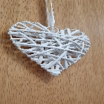 A white wicker heart hanging on a wooden door