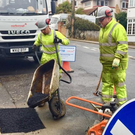 Workmen in hi visi jackets repairing the road