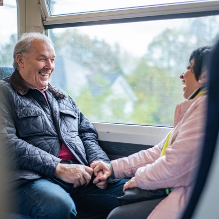 Man and woman sitting opposite each other on a train, holding hands.
