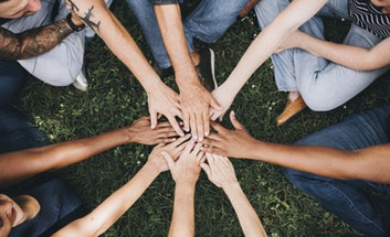 Young people in a circle with hands in the centre.