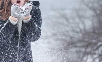 Woman blowing snow from hands.