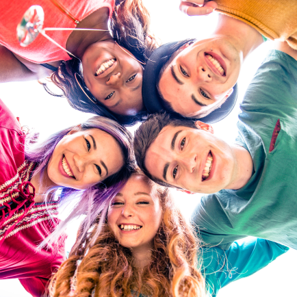 5 smiling children in rainbow colored tops bending over camera lens.